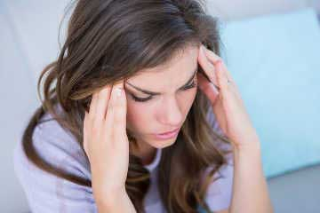 Sick woman suffering from head ache at home in the living room