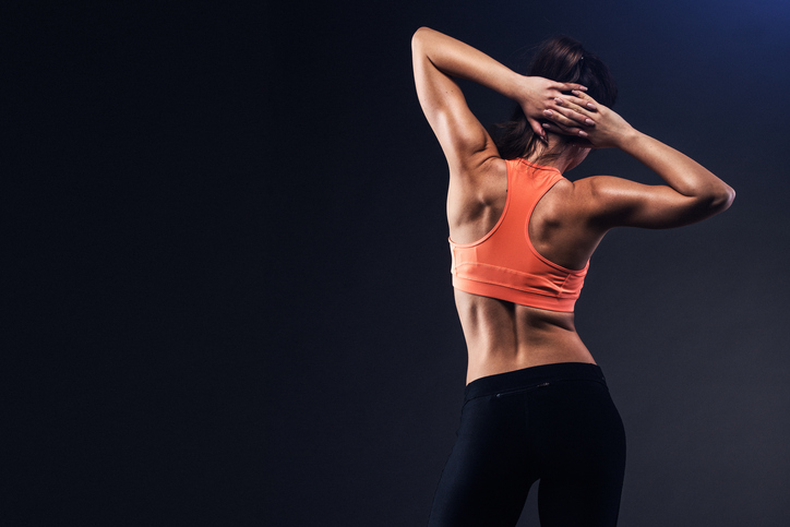 Back of beautiful athletic girl on a dark background. Young woman with muscular body. Fitness concept.