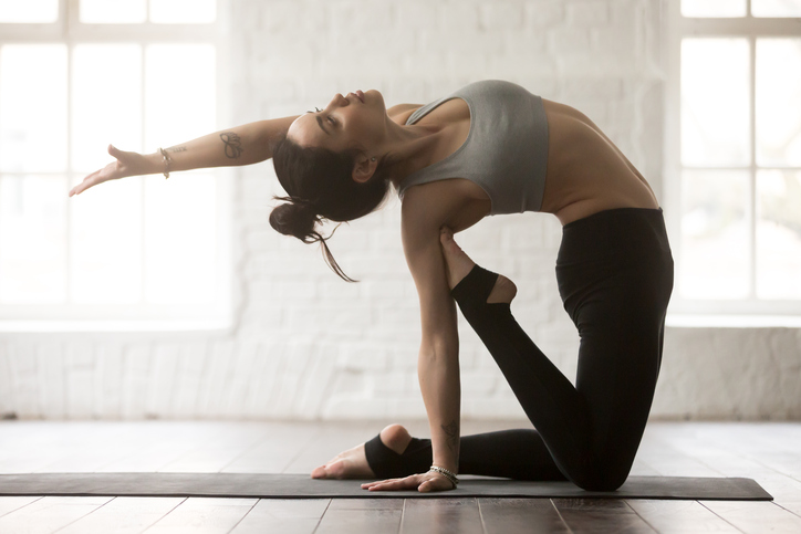 Young cool beautiful yogi woman practicing yoga concept, doing Ustrasana exercise, Camel pose, working out wearing sportswear bra and black pants, full length, white loft studio background. Side view
